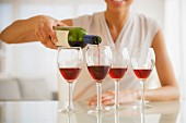A woman pouring red wine into four glasses