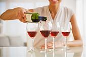 Frau giesst Rotwein in vier Gläser