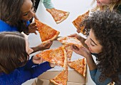 Women eating pizza together with their hands