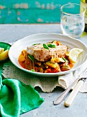 Tuna fish steak on a bean and tomato medley with lemons and basil