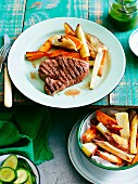 Grilled steak with sweet potatoes and root vegetables and salsa verde