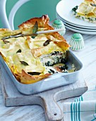 Rocket and ham lasagne with sage in a baking dish