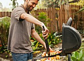 A man in a garden using tongs to turn food on the barbecue