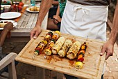 A man holding a wooden board of barbecued vegetable skewers and corn on the cob