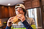 A teenage boy in kitchen eating a large sandwich
