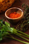 Paprika in a wooden bowl next to herbs