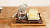 Pieces of butter, a jar and a sieve for making ghee