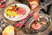 Rindfleischspiess am Tisch aufschneiden