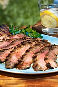 Sliced Grilled Flank Steak on a Blue Platter