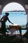 Junge Frau stellt Gläser auf Restauranttisch mit Blick aufs Meer