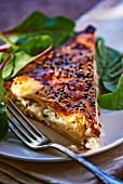 A slice of puff pastry tart with sesame seeds and feta cheese