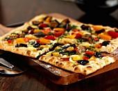 A vegetable tart with olives, sliced