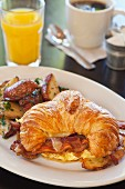 A croissant with scrambled eggs, bacon and cheese served with a side of sauteed potatoes, orange juice and coffee