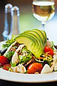 Cobb salad with avocado, tomatoes, bacon and chicken served with a glass of wine