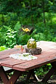 Linden blossom tea, honeycomb and redcurrants on a garden table