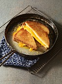 A grilled cheese sandwich being fried in a pan