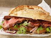 A grilled steak sandwich on parchment paper