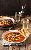 Seafood soup with tomatoes and grilled bread
