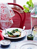 A poached egg and spinach sandwich served with pesto and water on a table