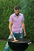 A young man barbecuing salmon trout fillet in the garden