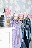 Florale Tapete hinter Vintage Kleiderhakenleiste mit Jeanskleidung; Retrovase mit Hortensienblüte auf weißer Kommode