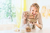 A blonde woman eating muesli