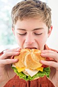 A teenager biting into a cheeseburger