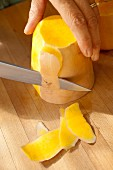 A butternut squash being peeled