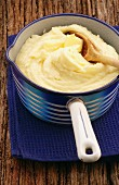 Mashed potatoes with a knob of butter in an enamel saucepan