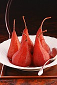 Red wine pears standing on a white plate