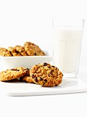 Three Oatmeal Raisin Cookies on a Green Plate with a Glass of Milk