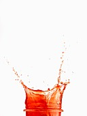 Red juice splashing from a glass