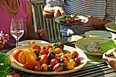 People eating tomatoes at a garden table in the summer