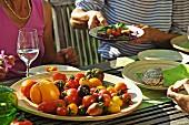 Menschen essen Tomaten auf einem sommerlichen Gartentisch