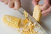 Corn kernels being scraped from a cob