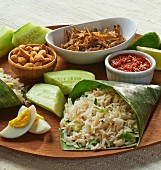Coconut rice in a banana leaf, eggs, fish, cucumber and a dip (Asia)