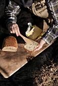 Frauenhände mit Butterbrot im Freien auf Holzbrett und Fell