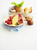 A small lunch plate with cheese, ham, bread, fruit and vegetables
