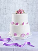 A two tier wedding cake decorated with candied flowers and petals