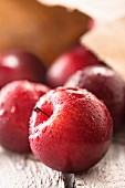 Freshly washed red plums with a paper bag in the background