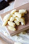 Handmade Sardinian gnocchetti (malloreddus) on a wooden plate with semolina