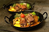 Leg of lamb and lamb ribs in a thyme sauce, and lamb ragout with bacon beans and polenta, East Tyrol, Austria