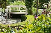 Geschwungene, niedrige Hecke um sonnigem Gartenplatz mit weisser Sitzbank
