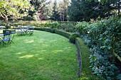 Rasenfläche mit geschwungener Heckeneinfassung, im Hintergrund Gartentische und Stühle