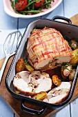 Stuffed turkey breast wrapped in bacon with roast potatoes