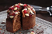 A mini Christmas cake with nuts and glace cherries, sliced