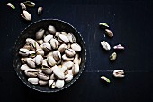 Pistachios in a silver bowl on a dark surface