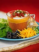 A layered tomato dip with cheese, olives and coriander (Mexico)
