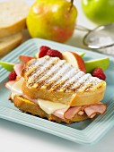 A Monte Cristo sandwich with ham, cheese, icing sugar and fresh fruit