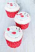 Raspberry and chocolate cupcakes decorated with singing birds